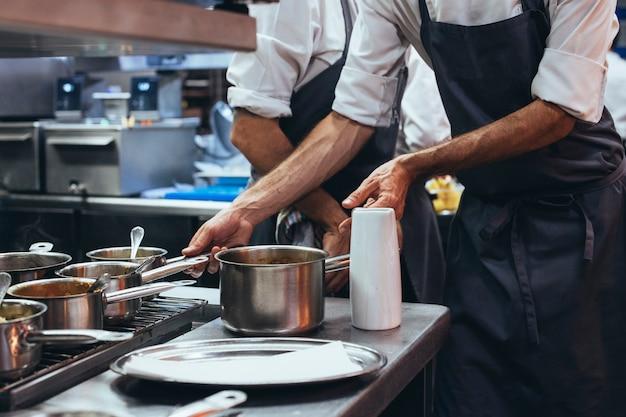 Cuoco unico irriconoscibile che cucina alimento in una cucina del ristorante