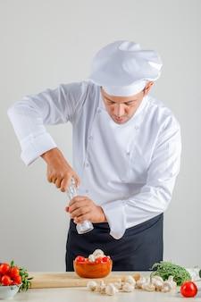 Cuoco unico maschio che aggiunge sale al cibo in uniforme, cappello e grembiule in cucina