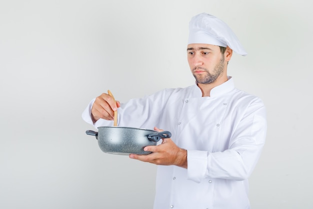 Cuoco unico maschio che mescola la minestra con il cucchiaio di legno in uniforme bianca