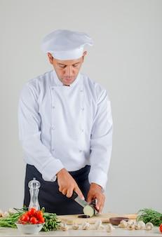 Cuoco unico maschio che taglia melanzana a pezzi sul bordo di legno in cucina in uniforme, cappello e grembiule