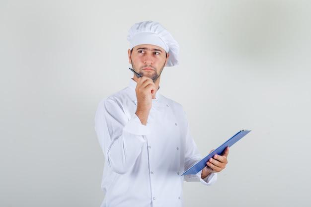 Cuoco unico maschio che tiene penna e appunti in uniforme bianca e guardando premuroso