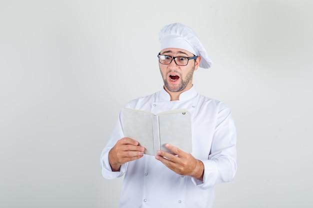Cuoco unico maschio in uniforme bianca, occhiali da lettura libro e sguardo sorpreso