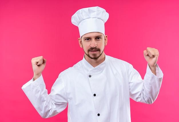 Cuoco unico maschio professionista cuoco in uniforme bianca e cappello da cuoco stringendo i pugni felici ed emozionati rallegrandosi del suo successo in piedi su sfondo rosa