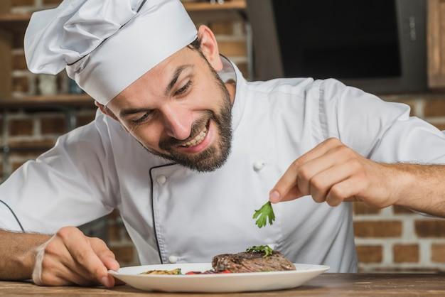 Cuoco unico maschio sorridente che decora il piatto dell'alimento