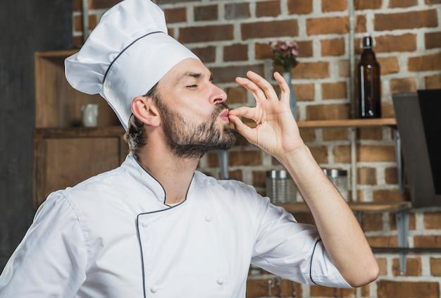 Cuoco unico professionista maschio che mostra il segno per delizioso