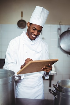Cuoco unico sorridente che fa le note su una lavagna per appunti