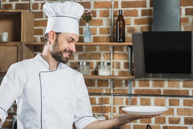 Cuoco unico sorridente che tiene un piatto bianco vuoto a disposizione