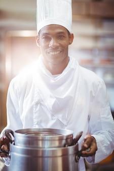 Cuoco unico sorridente nella tenuta della cucina che cucina vaso