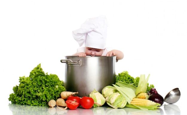 Cuoco unico sveglio del bambino con grande pentola e verdure