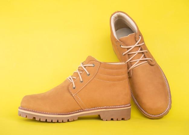 Cuoio degli stivali di giallo di modo dell'uomo isolato su giallo