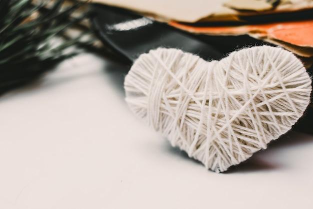 Cuore bianco a maglia e pila di vecchi dischi in vinile polverosi graffiati legati con la corda