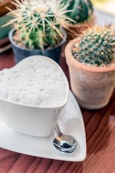 Cuore caldo di forma della tazza di caffè sul cactus della tavola