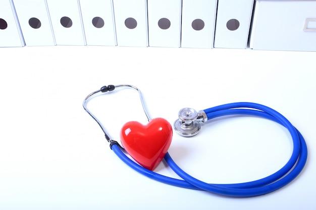 Cuore con uno stetoscopio medico, isolato su legno