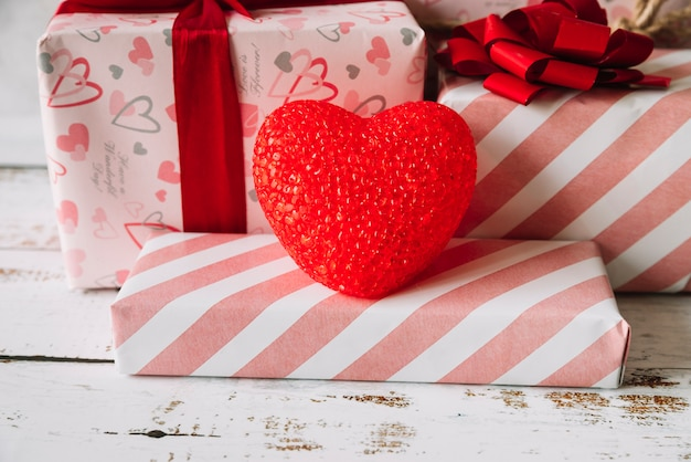 Cuore decorativo vicino a scatole regalo in involucro