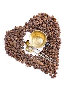 Cuore dei chicchi di caffè e tazza e cucchiai di antuque su bianco