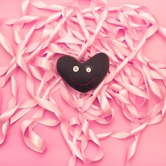 Cuore del giocattolo tessile sullo sfondo di una bobina di nastri di raso decorativi di colore rosa.