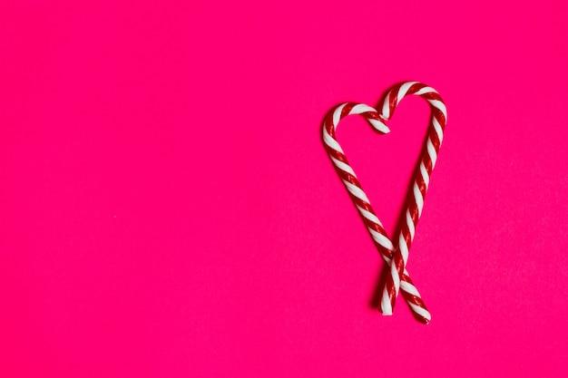 Cuore di caramelle di natale su sfondo rosa