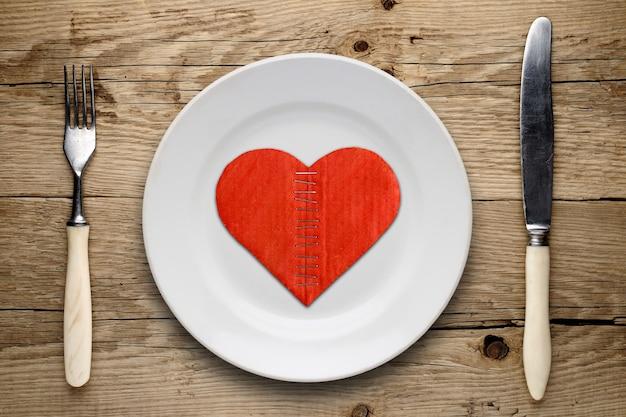 Cuore di cartone rotto sul piatto su legno