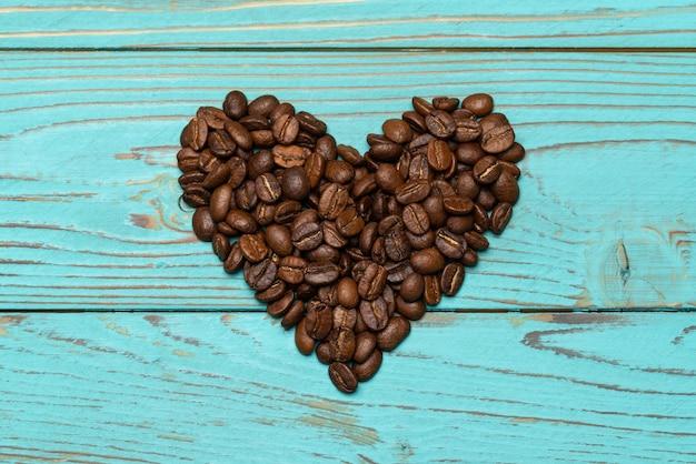 Cuore di chicchi di caffè sulla tavola di legno