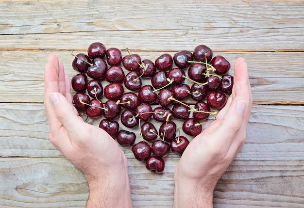 Cuore di ciliegie fresche e mature in mani maschili a coppa