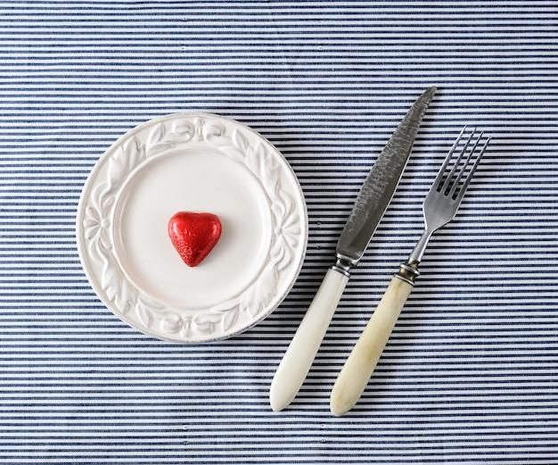 Cuore di cioccolato rosso su piatti e coltello con una forchetta
