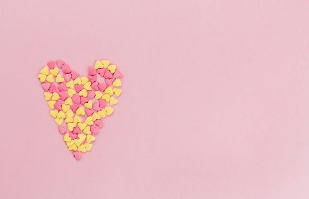 Cuore di confetti rosa e giallo confetti su uno spazio di copia sfondo rosa