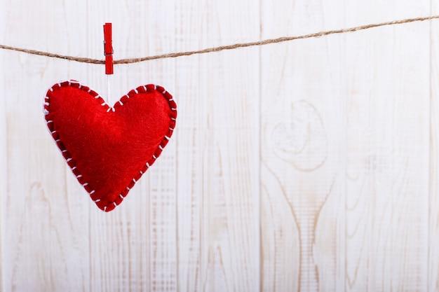 Cuore di feltro rosso su una corda, su fondo bianco in legno