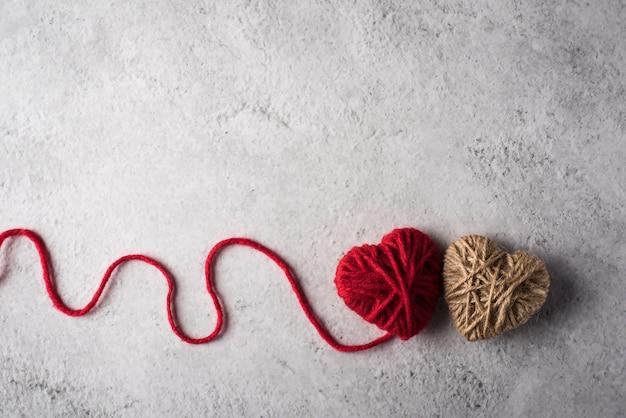 Cuore di filato rosso a forma di sullo sfondo del muro
