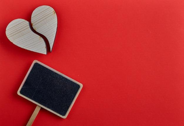 Cuore di legno di giorno di biglietti di s. valentino su fondo rosso