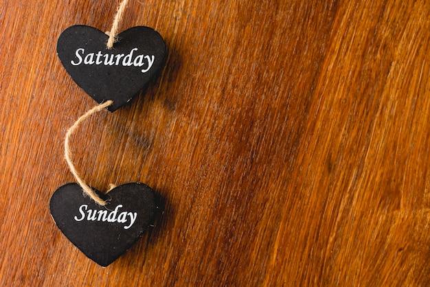Cuore di legno nero con i giorni del weekend scritto sopra.