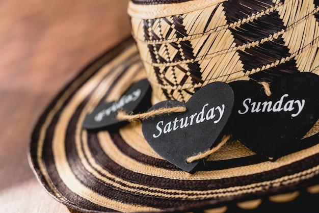 Cuore di legno nero con il nome di giorni di fine settimana sopra un cappello messicano.