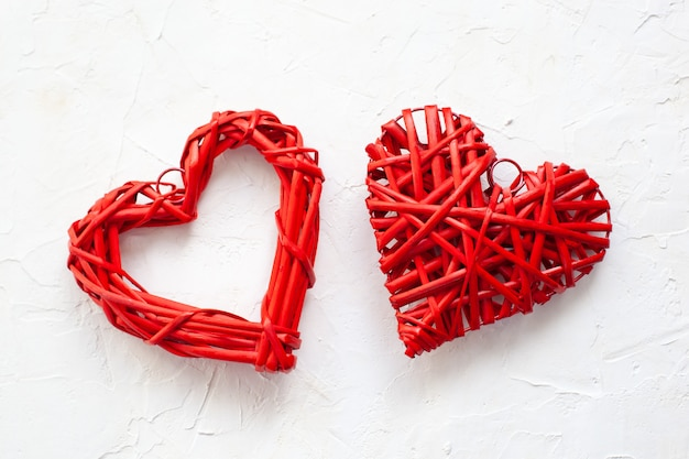 Cuore di legno rosso nello stile d'annata isolato su fondo concreto strutturato bianco. decorazioni per la casa rustiche per san valentino. a forma di cuore. concetto di carta di san valentino. medicina, salute, malattia. concetto di amore
