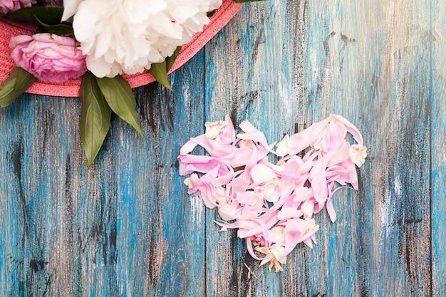 Cuore di petali e una parte di un mazzo di fiori su un tavolo di legno. san valentino o concetto di matrimonio