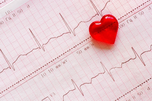 Cuore di plastica sullo sfondo dell'elettrocardiogramma (ecg). giorno del cuore sano