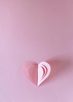 Cuore di san valentino, singoli simboli di carta di amore a forma di cuore su sfondo rosa