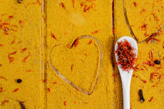 Cuore di spezie e condimenti. cucchiaio bianco con zafferano su curry