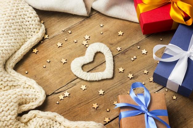 Cuore di tessuto, sciarpa lavorata a maglia, scatole regalo, ghirlanda luminosa su fondo in legno.