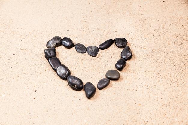 Cuore disegnato con ciottoli sulla sabbia della spiaggia