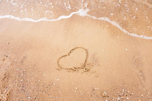 Cuore disegnato nella sabbia con l'onda del mare