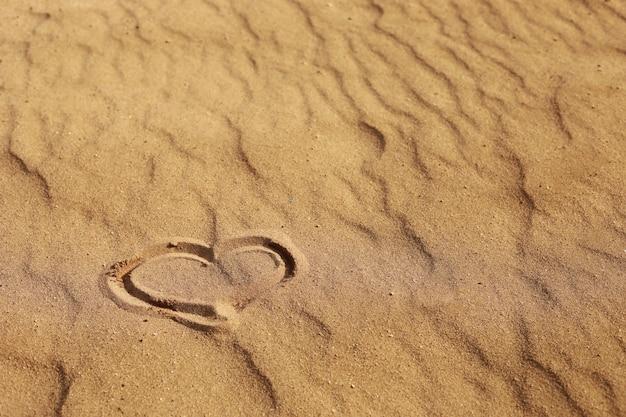 Cuore disegnato sulla sabbia, concetto di amore. rilassarsi sulla spiaggia di sabbia. copia spazio. san valentino su una spiaggia assolata.