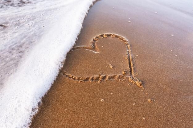 Cuore disegnato sulla sabbia della spiaggia, morbida onda del mare. concetto di amore.