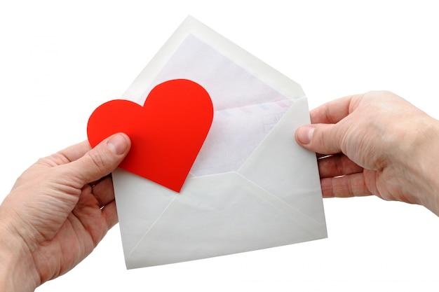 Cuore e busta del biglietto di s. valentino in mani isolate