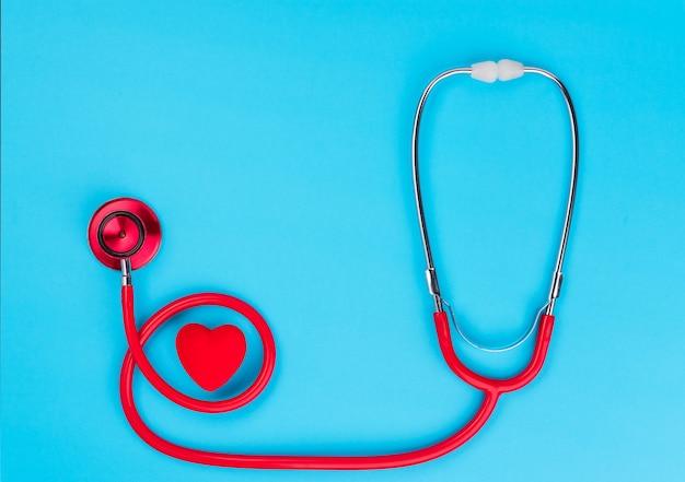 Cuore e stetoscopio rossi sopra sul blu.