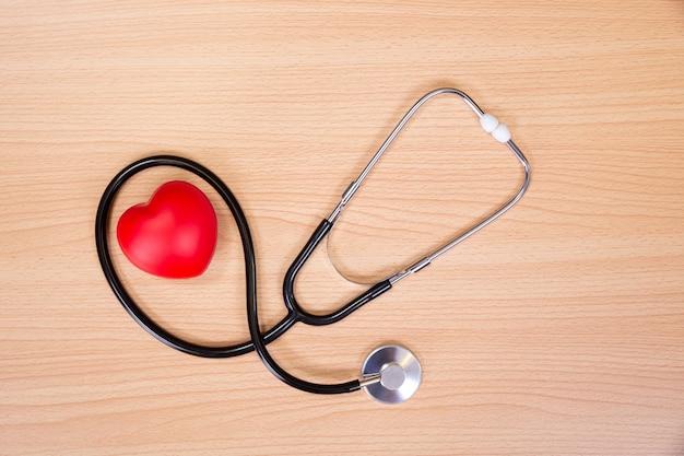 Cuore e stetoscopio rossi sulla tavola di legno. strumento medico per l'ascolto del battito cardiaco. concetto di assistenza sanitaria.