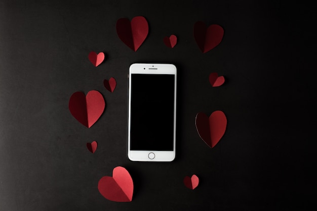 Cuore e telefono su sfondo nero muro