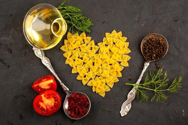 Cuore giallo crudo della pasta a forma di insieme con i pomodori rossi affettati erbe verdi olio d'oliva e spezie marroni sul pavimento scuro