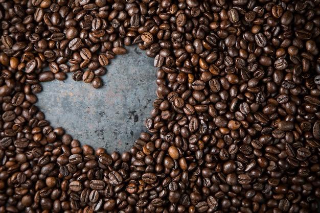 Cuore in chicchi di caffè su sfondo di metallo