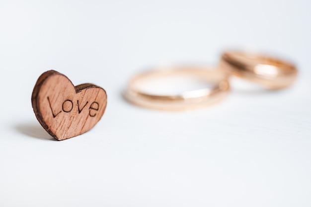Cuore in legno con iscrizione amore e coppia fedi nuziali su sfondo bianco. vista laterale.