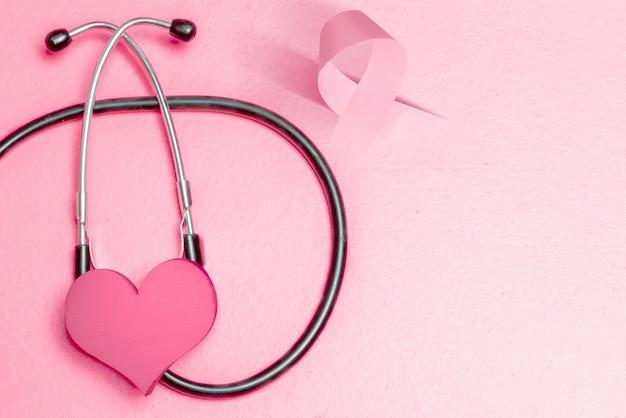 Cuore rosa e nastro di consapevolezza con uno stetoscopio