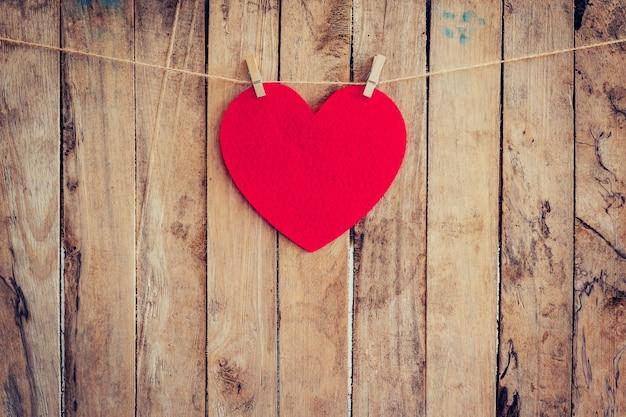 Cuore rosso appeso a clothesline e corda con sfondo in legno